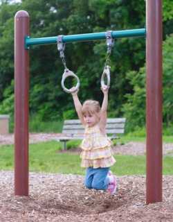 Girl hanging from Jungle gym