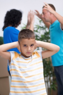Little boy trying not to listen to parent's argument