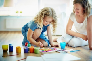 Child painting with parent