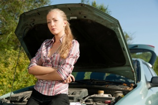 young woman with her broke down car