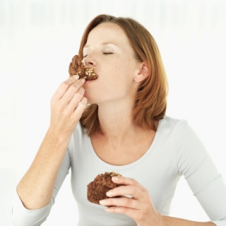 Young woman eating a muffin