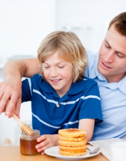 Adorable boy and his father putting syrup on waffles