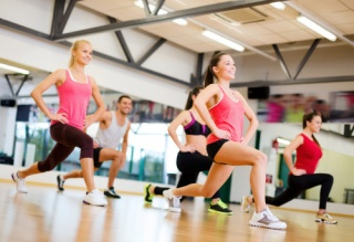 Group of smiling people exercising in a gym
