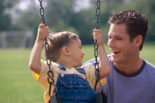 Father and son (4-5) playing on swing