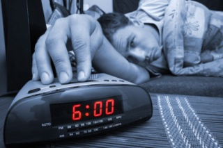 young man hitting snooze button