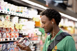 young man reading label on yogurt cup
