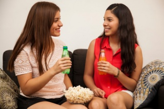 two teen girls with soda and popcorn