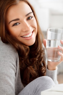 close-up, young woman holding glass of water