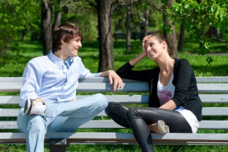 Couple sitting on park bench talking