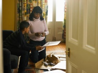 Mother and son (12-13) working together in living room, boy holding instruction manual